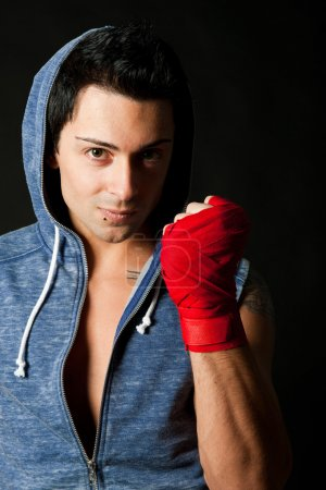 Portrait of young boxer on dark background