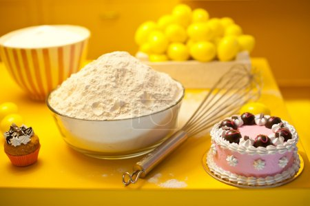 Photo for Baking ingredients with eggbeater and cake on a yellow kitchen background - Royalty Free Image