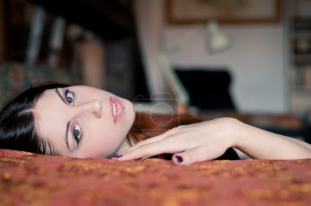 Portrait of a sensual young woman lying on sofa. Shallow depth of field