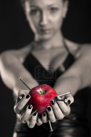 Conceptual image of beautiful girl with nails driven apple. Shallow depth of field