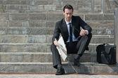 joven empresario con periódico sentado en las escaleras
