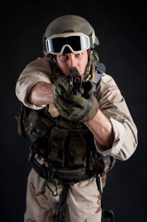 Soldier pointing gun against black background