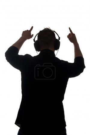 Man silouette with ear-phones listening to music against white background