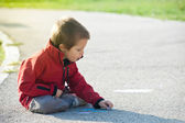 Kid playing on the ground with chalk