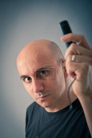 Foto de Hombre calvo con tomar foto de sí mismo con temporizador. fondo azul - Imagen libre de derechos