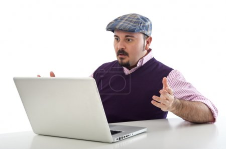 Portrait of a surprised young man looking at laptop against white background