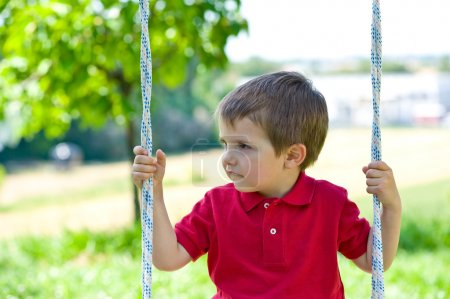 Small kid swinging on a sunny day with trees in the background