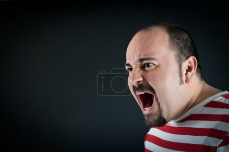 Angry man shouting against black background