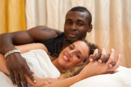 Interracial young happy couple relaxed in bed. Focus on hands