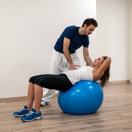 Woman exercising with her personal trainer at the gym