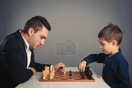 Man and child playing chess, isolated on dark background