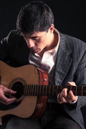 Man playing guitar against black background.