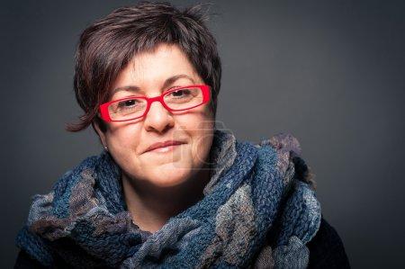 Foto de Mujer de mediana edad con gafas rojas cerrar retrato sobre fondo oscuro - Imagen libre de derechos