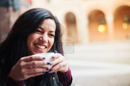 Smiling woman drinking coffee in a cafe outdoors. Shallow depth of field.