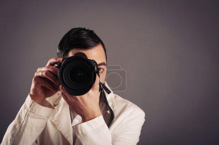Photo pour Homme tenant la caméra sur fond sombre . - image libre de droit