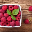 Raspberries in bowl on wooden table background. To...