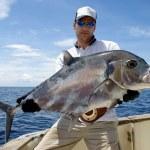 Big game fishing - Happy fisherman holding a treva...