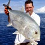 Big game fishing. Happy fisherman holding a treval...
