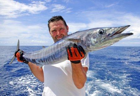 Photo pour Pêcheur tenant un poisson gros wahoo. - image libre de droit