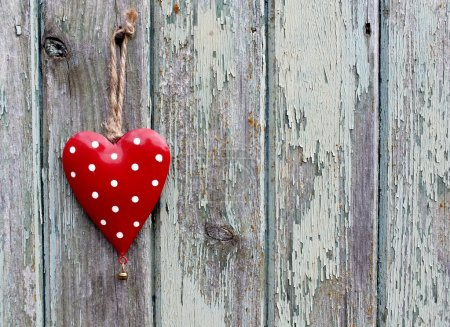 Shabby chic red and white spotty heart on grunge wooden background