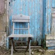 Shabby chic wooden chair with blue weathered grunge background
