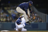MIGUEL TEJADA jumps to avoid JAMES LONEY after he threw to first to complete a double play during the game