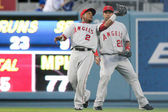 Erick Aybar back pedals to catch a fly ball while Juan Rivera looks on during the match