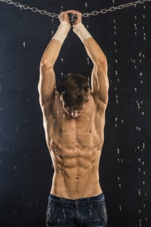 Image of muscle man with chains posing in aqua studio