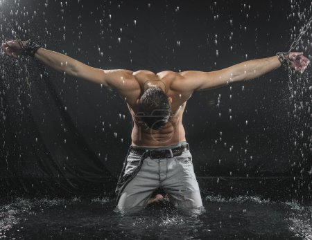Photo for Trong man in chains posing under the rain, aqua studio - Royalty Free Image