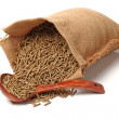 Bag of rabbit feed with wooden spoon on white back...