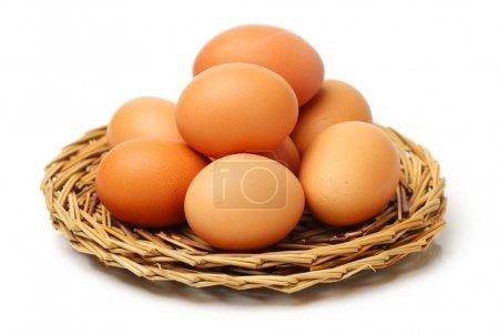 Photo pour Tas d'oeufs de poules sur des plaques bruns tressés isolés sur fond blanc - image libre de droit