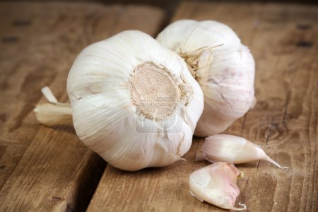 Organic garlic whole and cloves on the wooden back...
