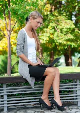 Photo for Young business woman sitting on a park bench and using laptop outdoors - Royalty Free Image