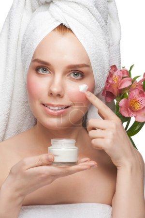 Woman applying moisturizing cream