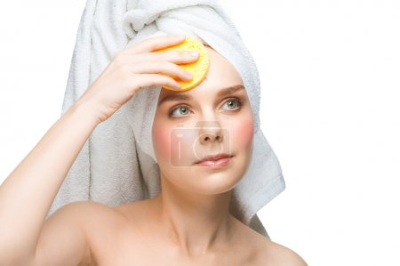 Woman with sponge cleaning her face
