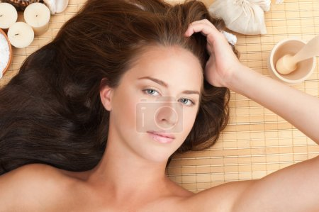 Photo for Close-up portrait of young beautiful spa woman with long brown hair lying on bamboo mat at spa salon - Royalty Free Image
