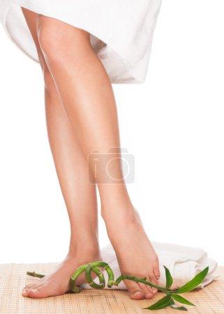 Photo pour Photo gros plan d'une femelle pieds avec bambou vert au salon de spa sur la procédure de pédicure - image libre de droit