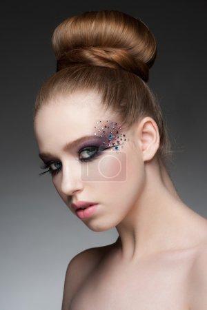 Photo pour Portrait de jeune femme belle avec maquillage mode lumineux avec strass et chignon coiffure - image libre de droit