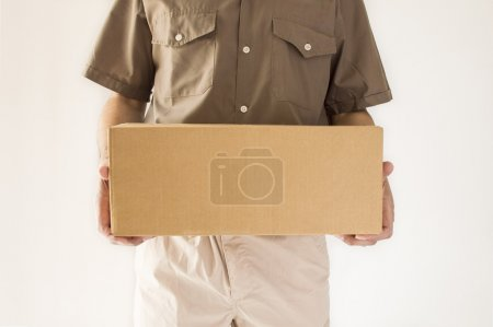 Photo for Postman having a packet for you standing in close up - Royalty Free Image
