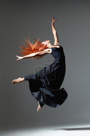Photo pour Jeune belle danseuse aux cheveux roux sautant sur fond de studio sombre - image libre de droit
