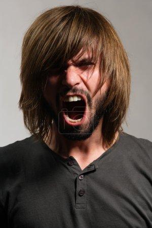 Photo pour Jeune homme criant avec une barbe et les cheveux longs - image libre de droit