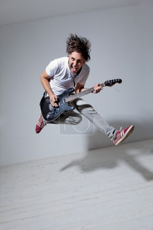Photo for Young man playing on electro guitar and jumping - Royalty Free Image