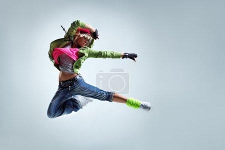Hip-hop dancer jumping on a studio background