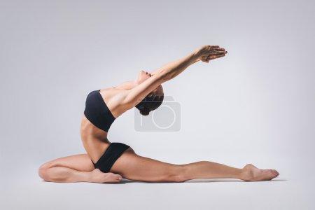 Photo pour Yoga de bel jeune posant sur un fond gris studio - image libre de droit