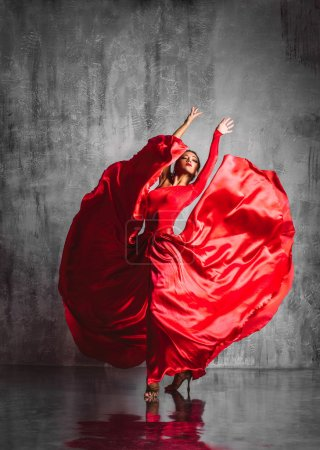 Photo for Dancer in red dress posing on studio background - Royalty Free Image