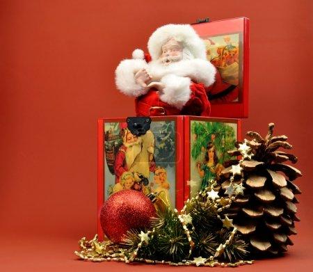 Photo pour Un Père Noël vintage, Saint Nicolas, le Père Noël Jack-in-the-Box avec des scènes de Noël de style vintage décoratif, avec boule rouge pailleté, cône de pin doré et des cordages de style festif sur un fond orange rouge élégant . - image libre de droit