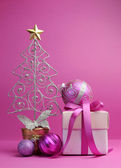Pink theme Christmas tree, gift and baubles festive holiday still life.
