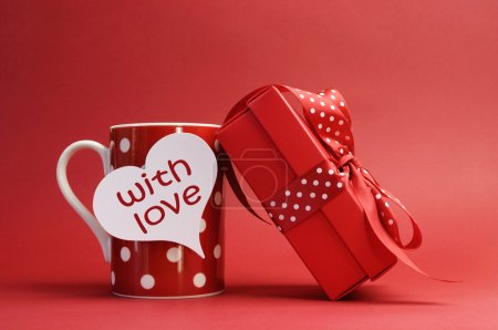"Photo pour ""With love"" message on red polka dot mug and red gift with polka dot ribbon bow against a red background for a bright, fun and cheerful Valentines Day. - image libre de droit"