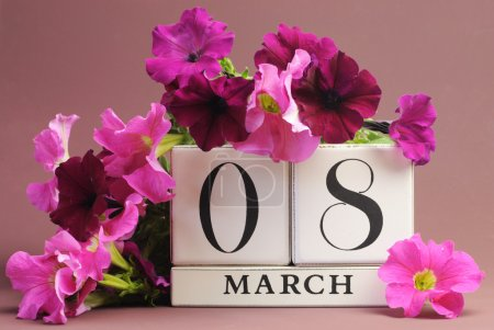 Photo for Save the date white block calendar for International Women's Day, March 8, decorated with pink and purple flowers against a pink purple background. - Royalty Free Image