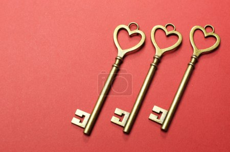 Three 3 gold keys on red background.